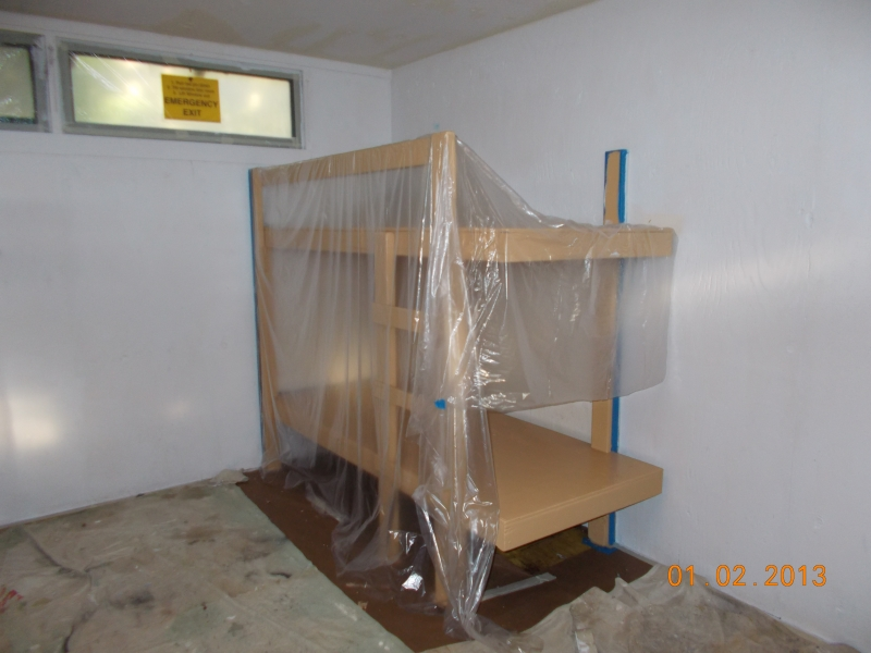 Painted bunk covered while walls get fresh coat of paint in St. Cecilia cabin in Fircrest Unit.