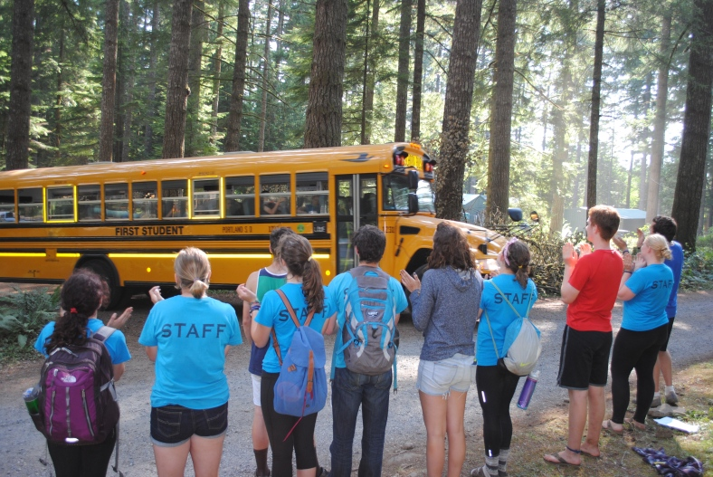 Camp Howard Summer Staff sing to departing campers as the last bus rolls out of camp for the summer camping program.