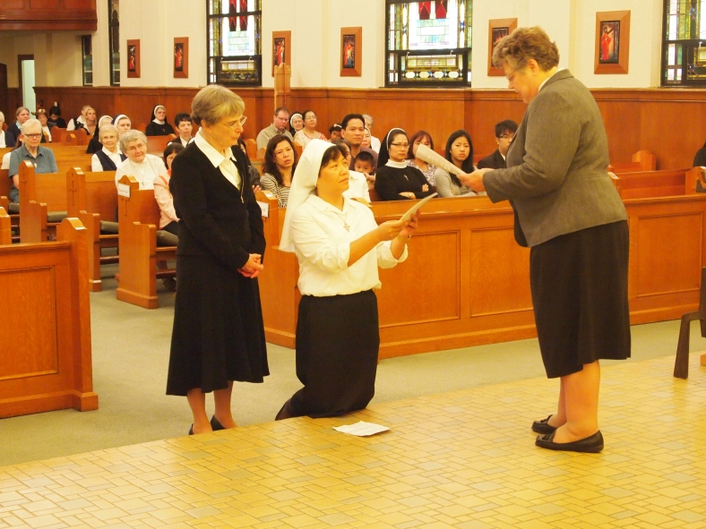 Sister Anna Nguyen receives the constitution of the Sisters of St. Mary of Oregon from Sister Charlene Herinckx, the religious leader of the Sisters.