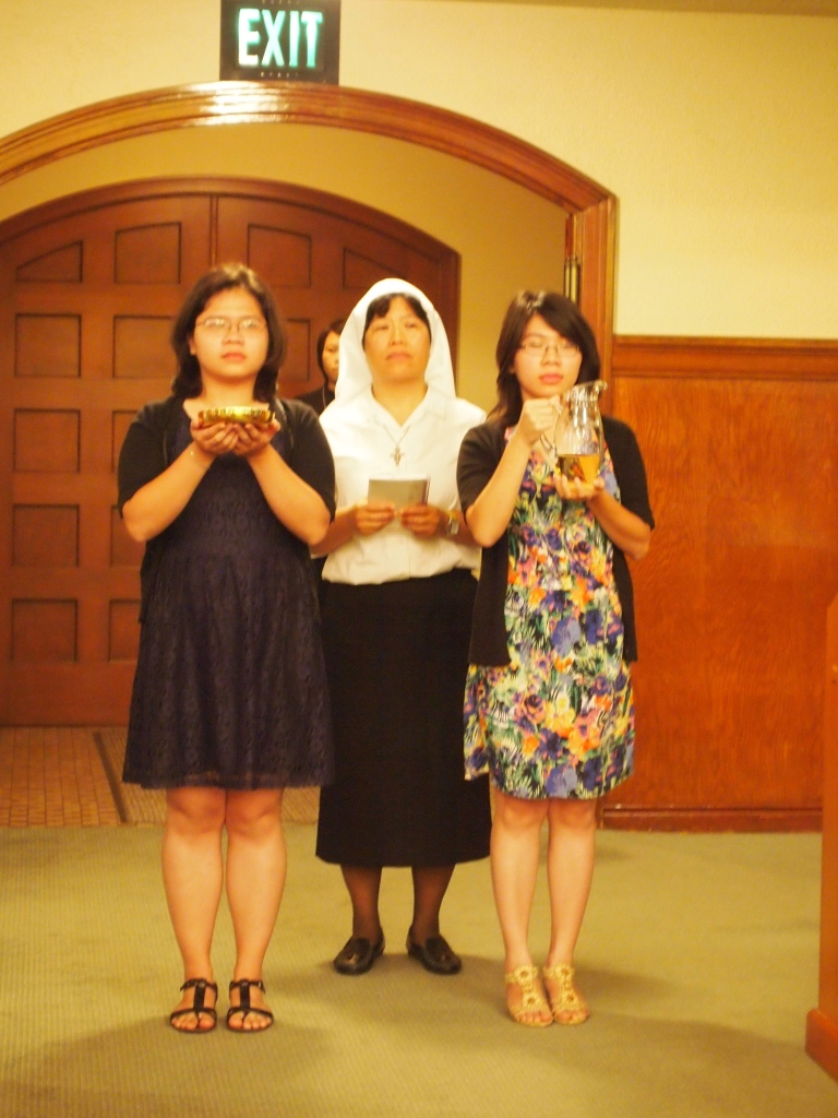 Sister Anna Nguyen and relatives bring gifts to the altar