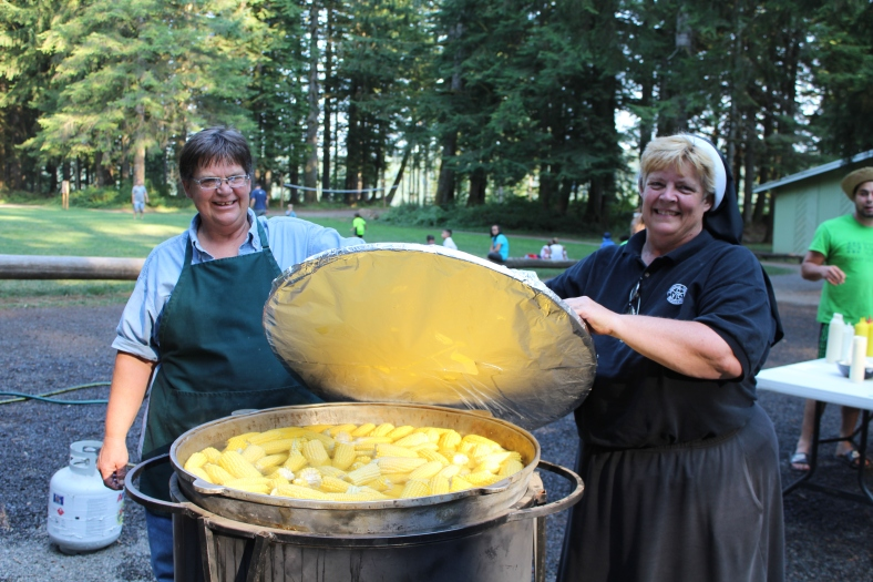 Karen von Borstel and Sr. Krista von Borstel open the lid to the wok to show the corn being cooked for Family Campers!