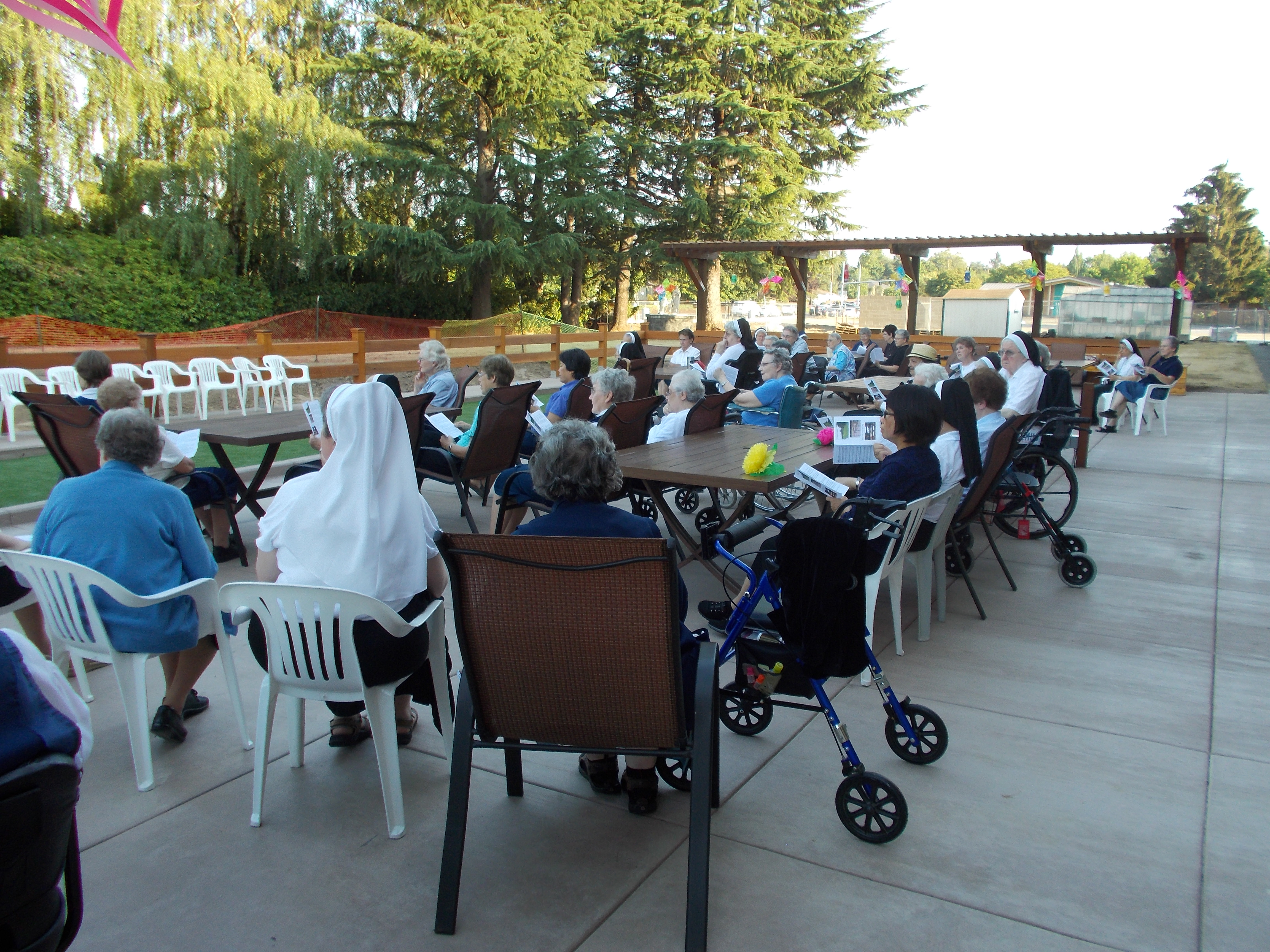 Sisters enjoy the chairs, tables and environment as they engage in the dedication service for the dedication of the new patio and bocce court.