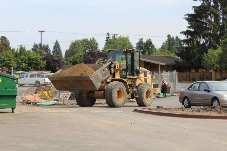 moving dirt around to make room for a new location for the dumpster near the new parking lot.