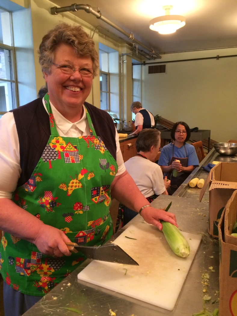 Sister Charlene cuts the ends off the ear of corn!  Look out folks! That's a big cleaver!